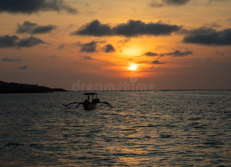 Zonsondergang over kalme oceaan met Balinese boot royalty-vrije stock afbeelding