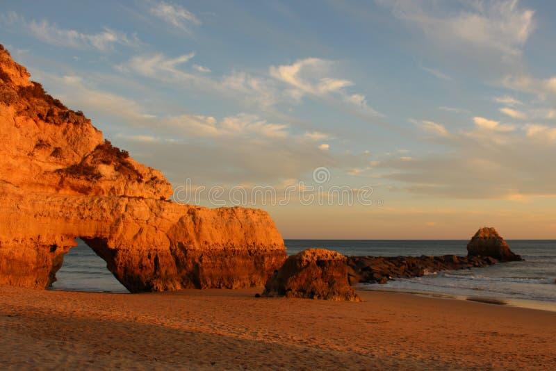 Zonsondergang over klippen bij verlaten strand in Algarve, Portugal stock foto's