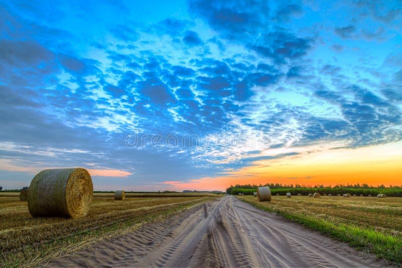 Zonsondergang over landelijke weg en hooibalen royalty-vrije stock afbeelding