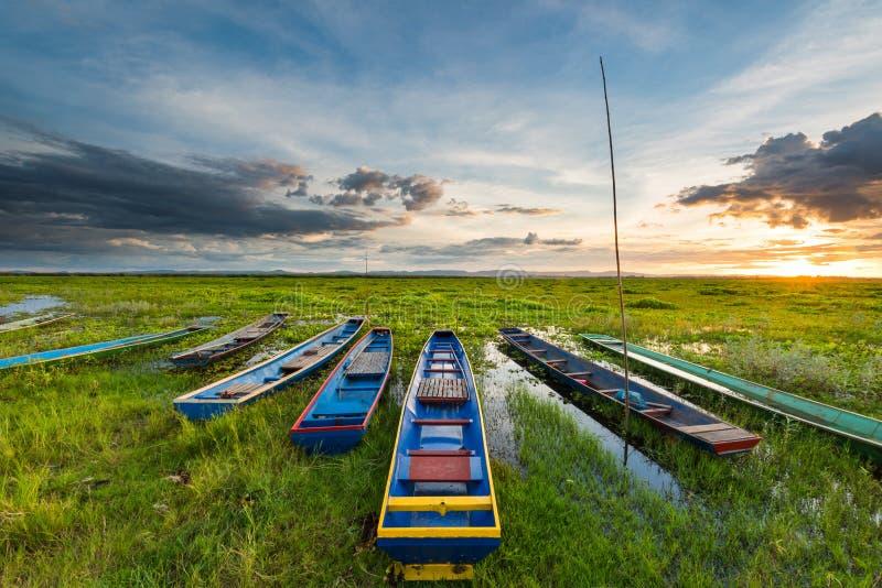 Zonsondergang over moeras met kleurrijke houten oude boten royalty-vrije stock afbeeldingen