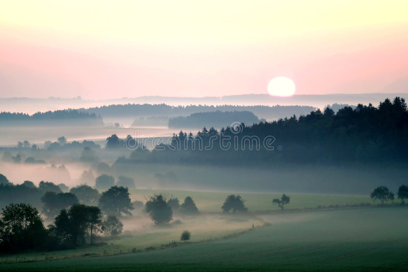 Zonsondergang over nevelig landschap royalty-vrije stock foto