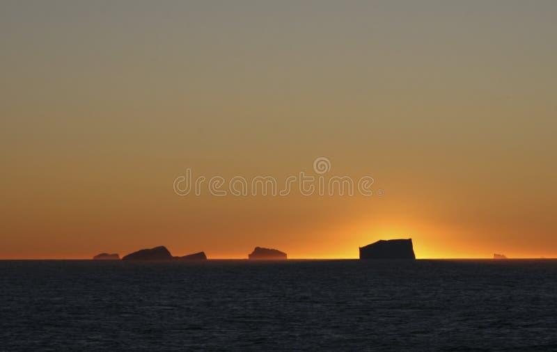 Zonsondergang over oceaanijsbergen stock fotografie