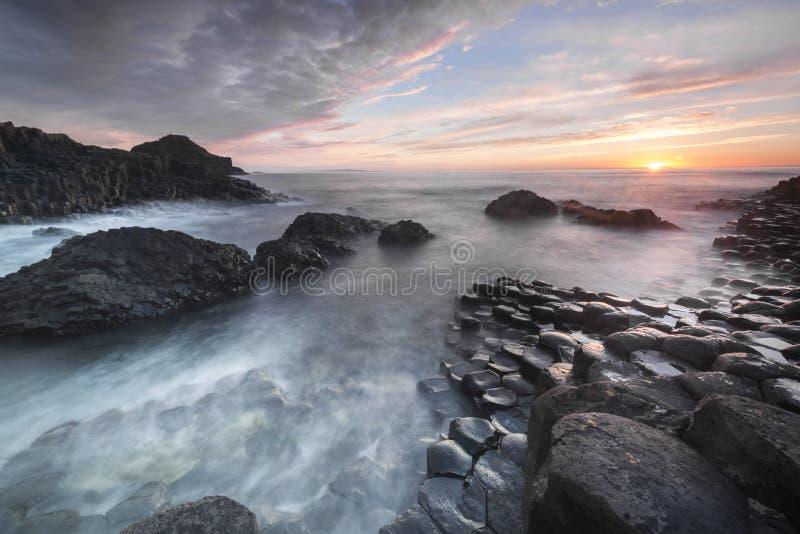 Zonsondergang over Reuzenverhoogde weg, Noord-Ierland royalty-vrije stock foto