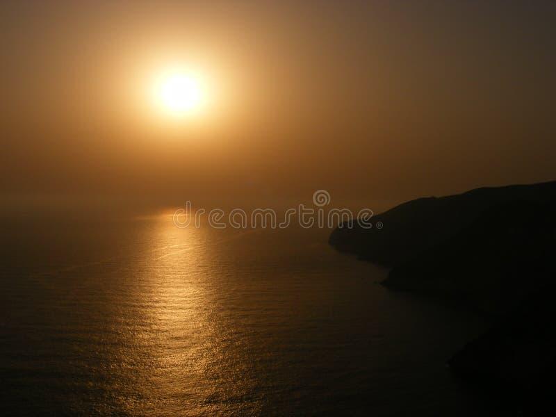 Zonsondergang over rotsachtige klippen stock afbeeldingen