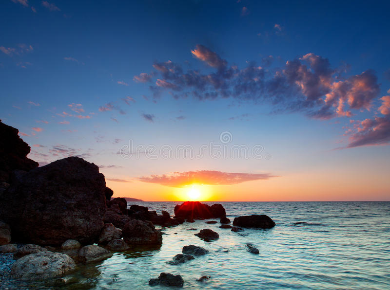 Zonsondergang over rotsachtige kust