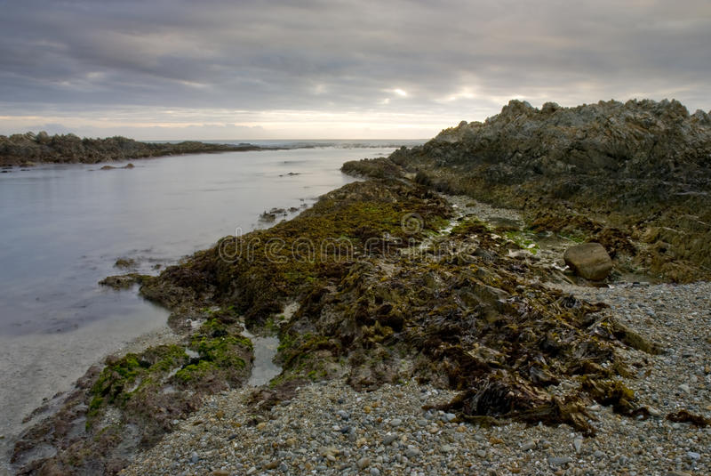 Zonsondergang over rotsachtige strand en overzees stock afbeelding