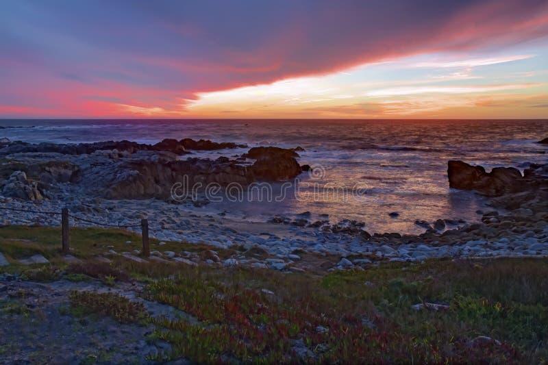 Zonsondergang over rotsen en zand bij Asilomar-het Strand van de Staat in Californië royalty-vrije stock foto's