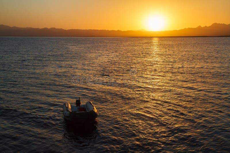 Zonsondergang over rubberboot stock foto