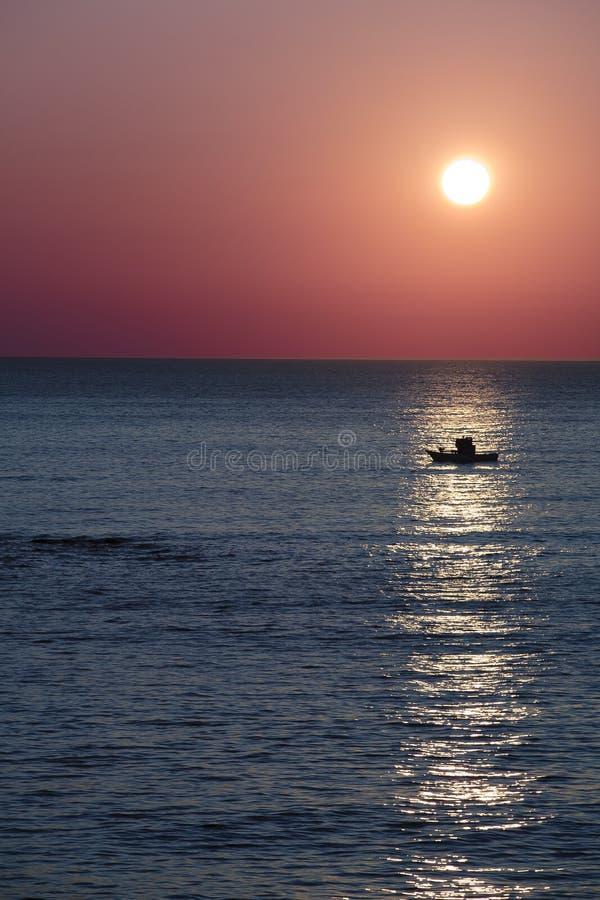 Zonsondergang over vissersboot stock foto's