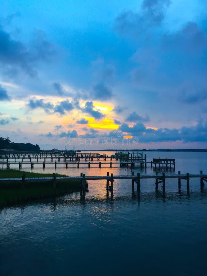 Zonsondergang over water met verscheidene dokken stock foto's