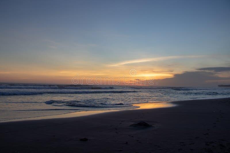 Zonsondergang over zandstrand van Changgu-het strand van de gebiedsecho, het eiland van Bali, binnen royalty-vrije stock foto's