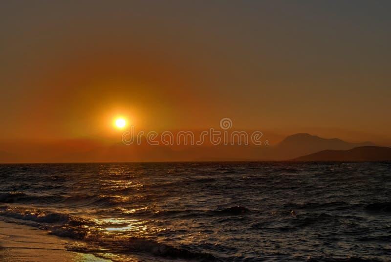 Zonsondergang, overzees en bergen royalty-vrije stock foto's