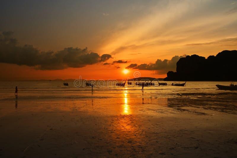 Zonsondergang overzees strand met de lange silhouetten van de staartboot royalty-vrije stock fotografie