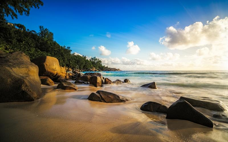 Zonsondergang in paradijs schaduwen van rotsen, tropisch strand, anse intendan stock fotografie