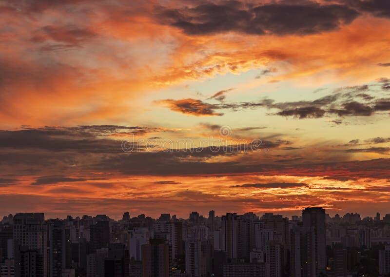 Zonsondergang in stad met industriële horizon en wolken stock afbeeldingen