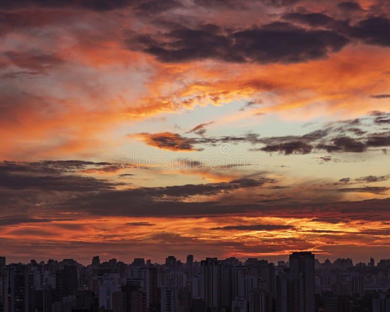 Zonsondergang in stad met industri?le horizon en wolken stock foto's