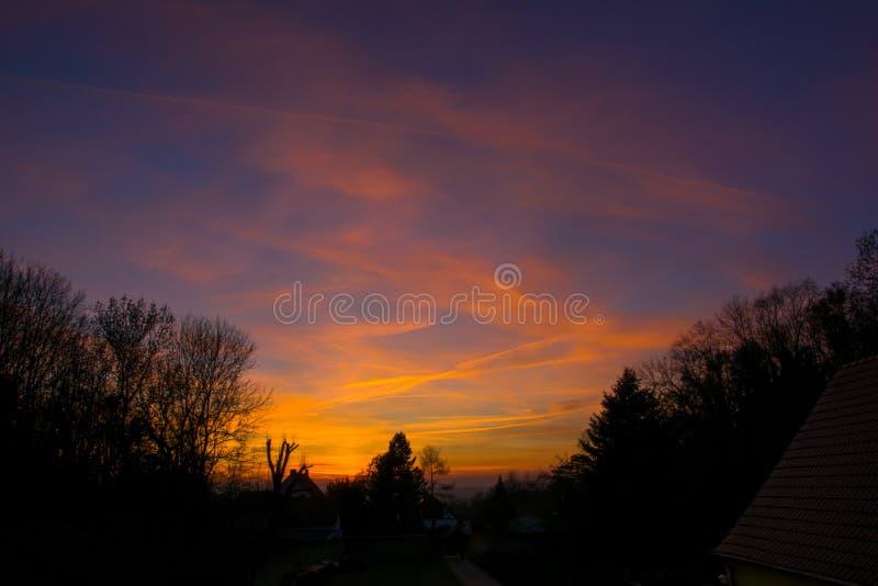 Zonsondergang tegen een donker silhouet royalty-vrije stock foto
