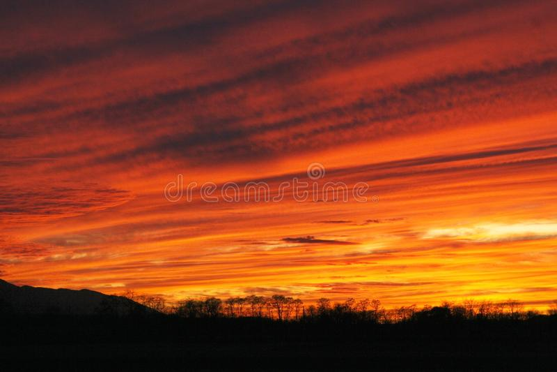 Zonsondergang in uitbarsting het oranje en heldere gele vegen over de hemel in stroken royalty-vrije stock foto