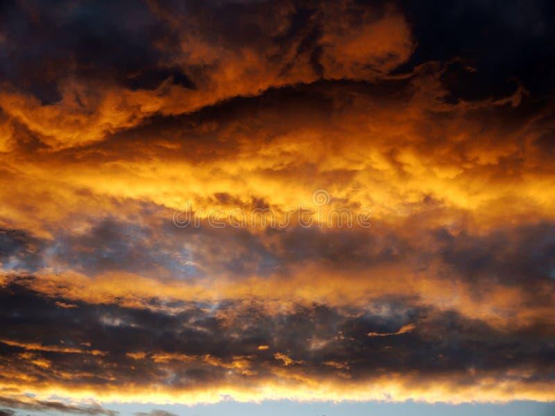 Zonsondergang vóór een nachtonweersbui met regen thunderclouds stock fotografie