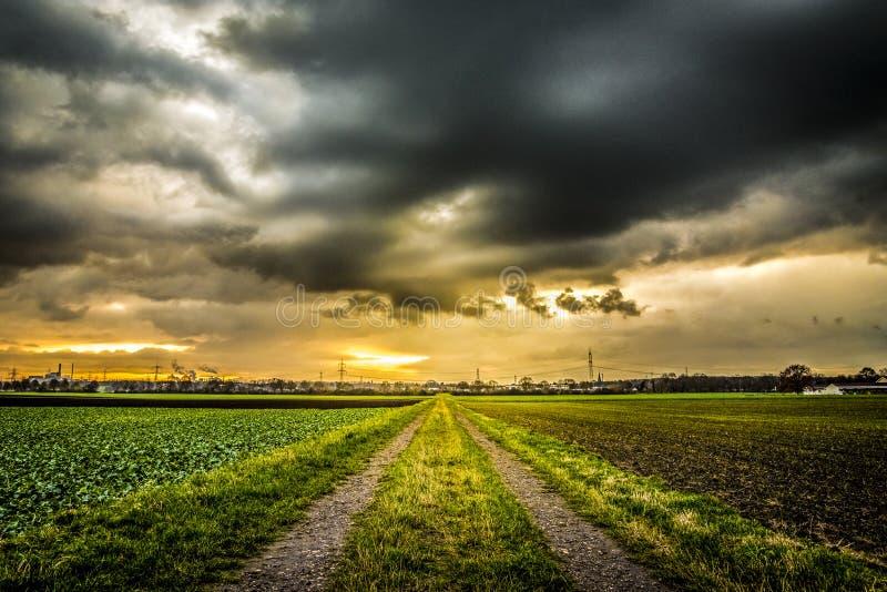 Zonsondergang van de landweg de dramatische hemel stock foto's