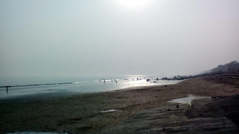Zonsondergang van de strandkant met sommige mensen die activiteit weg doen voor stock afbeeldingen