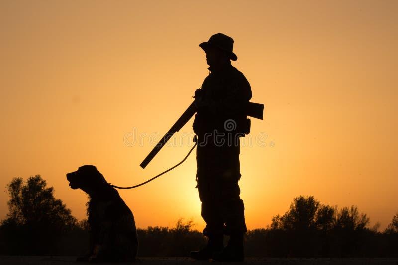 Zonsondergang van jager met een hond stock foto's
