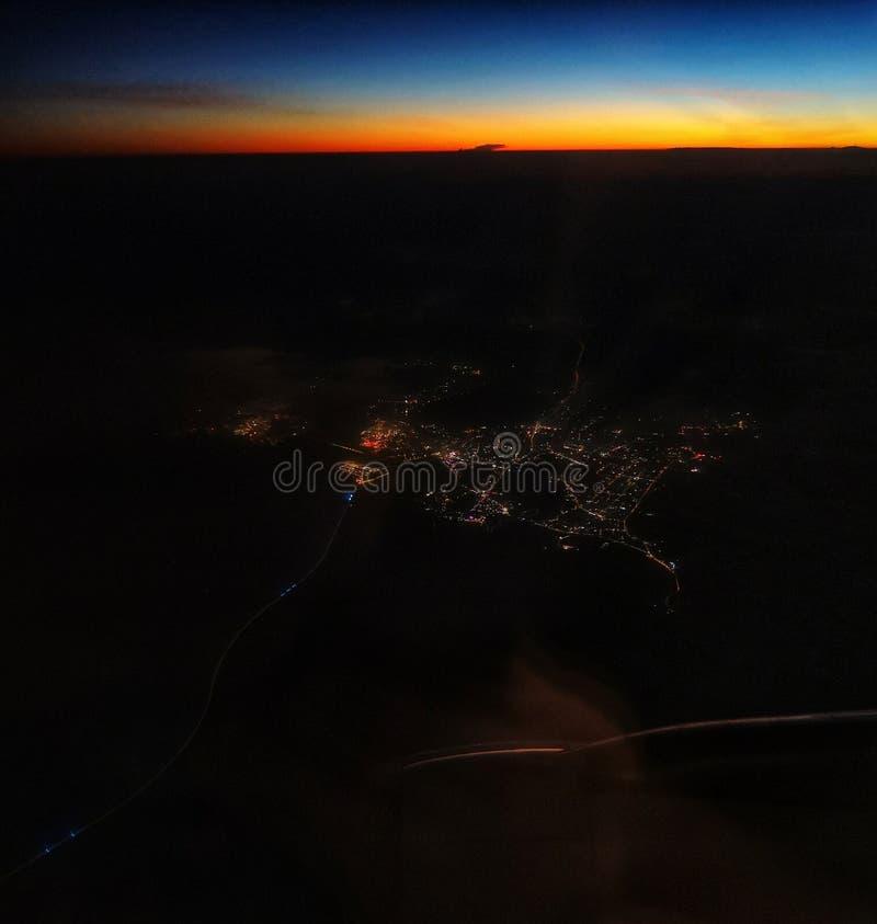 Zonsondergang van vliegtuig met stadslichten royalty-vrije stock afbeeldingen