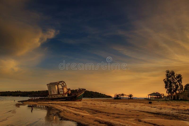 zonsondergang, Verlaten oude boot op een verlaten strand stock afbeeldingen