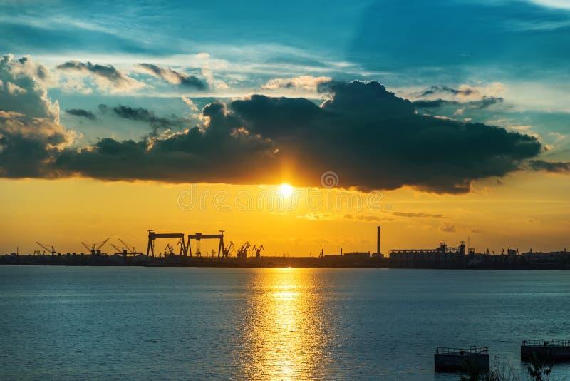 Zonsondergang in wolken over rivier en scheepsbouwfabriek stock afbeelding
