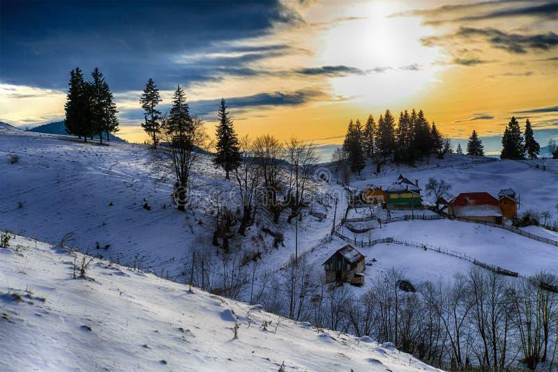zonsondergangberg over een klein dorp stock afbeelding
