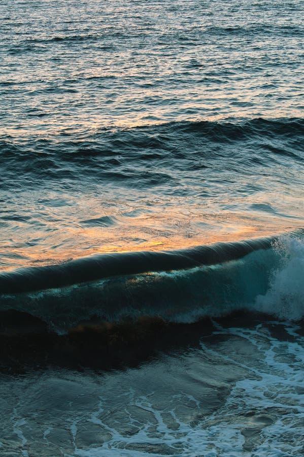 Zonsondergangbezinningen over de oceaanoppervlakte met plonsen royalty-vrije stock afbeelding