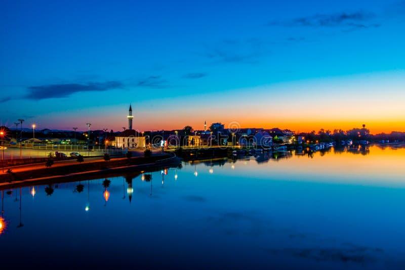 Zonsondergangbezinningen over stad en rivier stock afbeelding