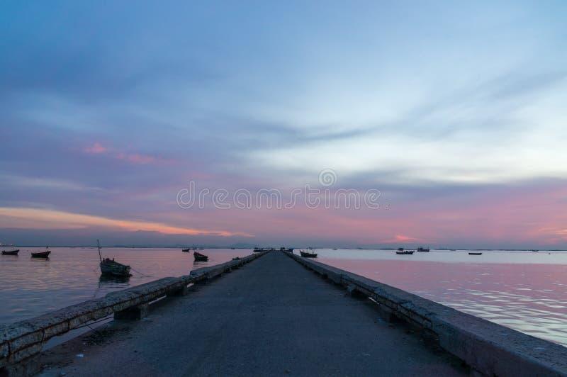 Zonsonderganghemel met haven en silhouet van kleine vissersboten stock afbeelding