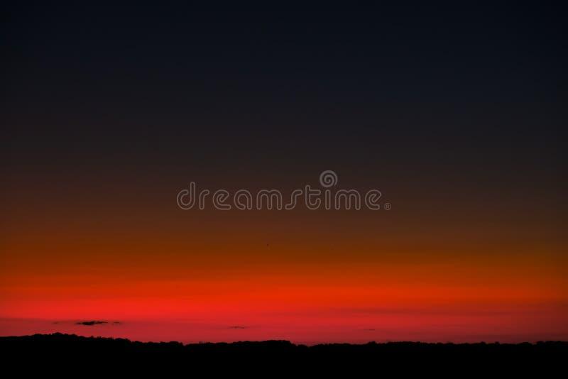 Zonsonderganghemel met heldere rode horizon en toenemende maan stock fotografie