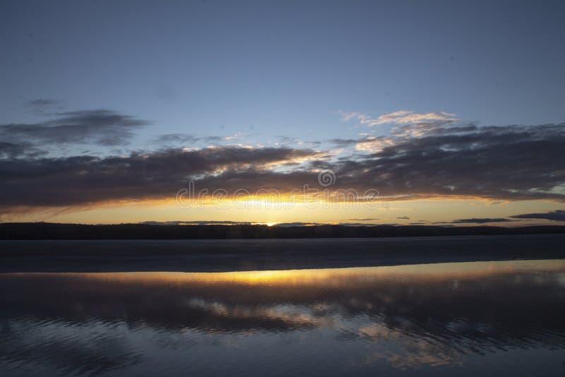 Zonsonderganghemel op het meer met wolken stock foto