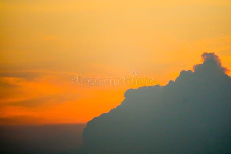 zonsonderganghemel terug op donkere silhouetwolk en sinaasappel van zonstraal stock afbeelding
