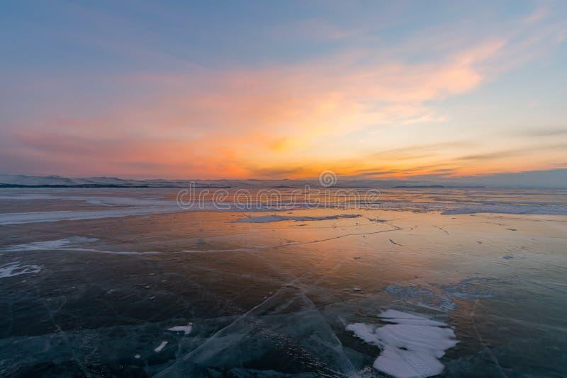 Zonsonderganghorizon over bevroren watermeer in wintertijd stock foto