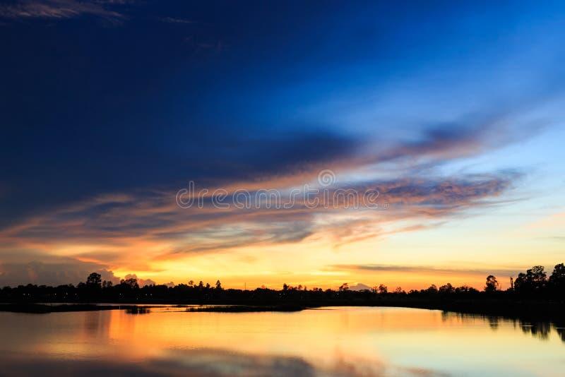 Zonsonderganglandschap met hemel bij het kalme meer stock afbeelding