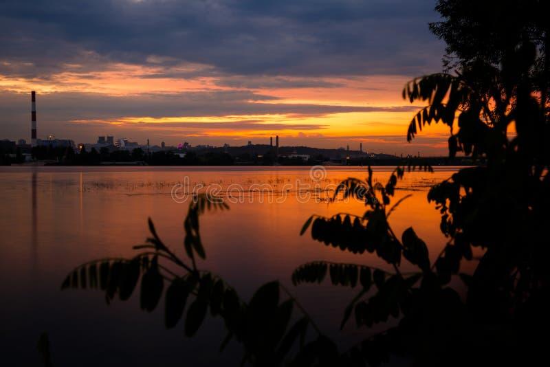 Zonsonderganglandschap over Dnipro-rivier tegen Kyiv-cityscape stock foto