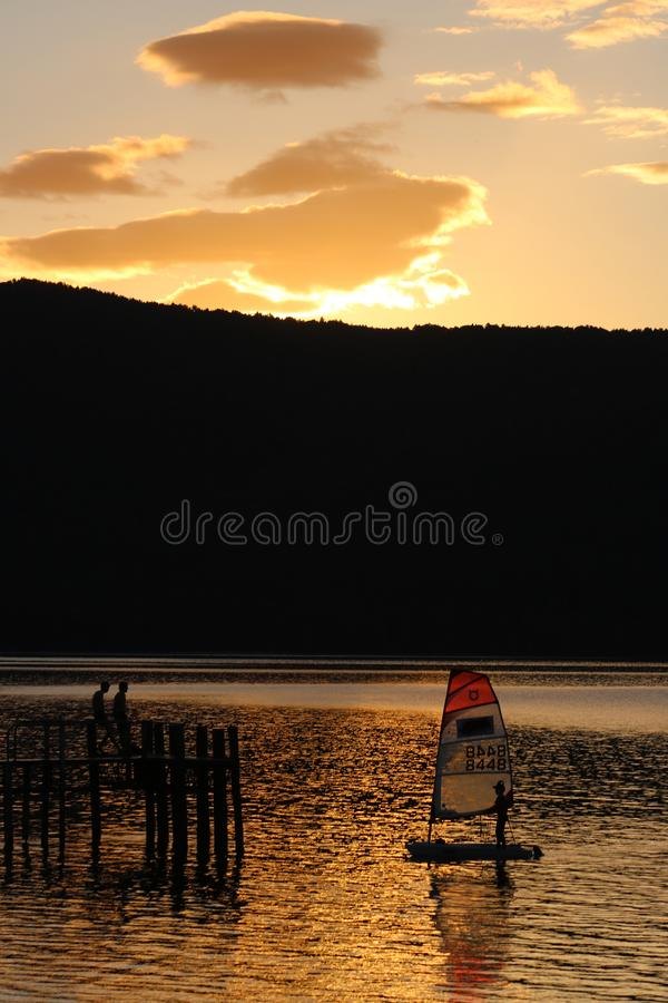 Zonsondergangmeer Te Anau met kleine jacht en pier stock foto