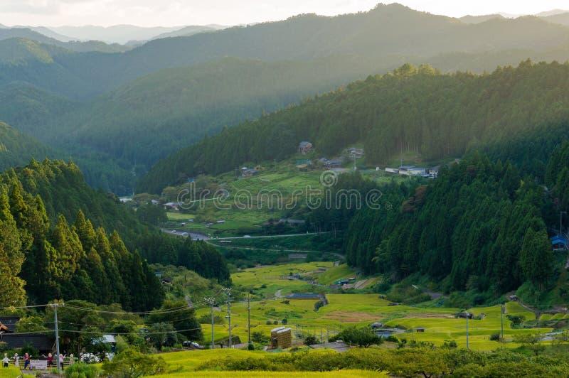 Zonsondergangmening met zonstralen over plattelandsbergen, padieveld royalty-vrije stock fotografie