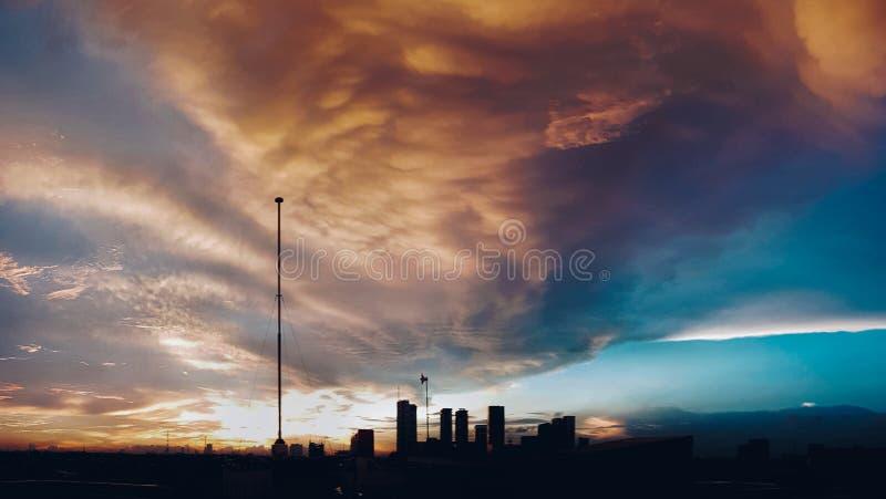 Zonsondergangmening op hoogste kantoor en wat wolk en de bouwachtergrond stock fotografie