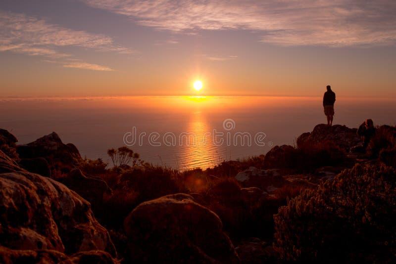 Zonsondergangmeningen met silhouet van een mens stock fotografie