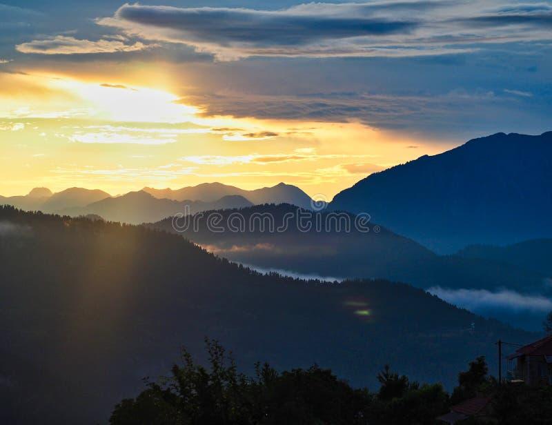 Zonsondergangnagloeiing achter Griekse Bergketen, Griekenland stock foto