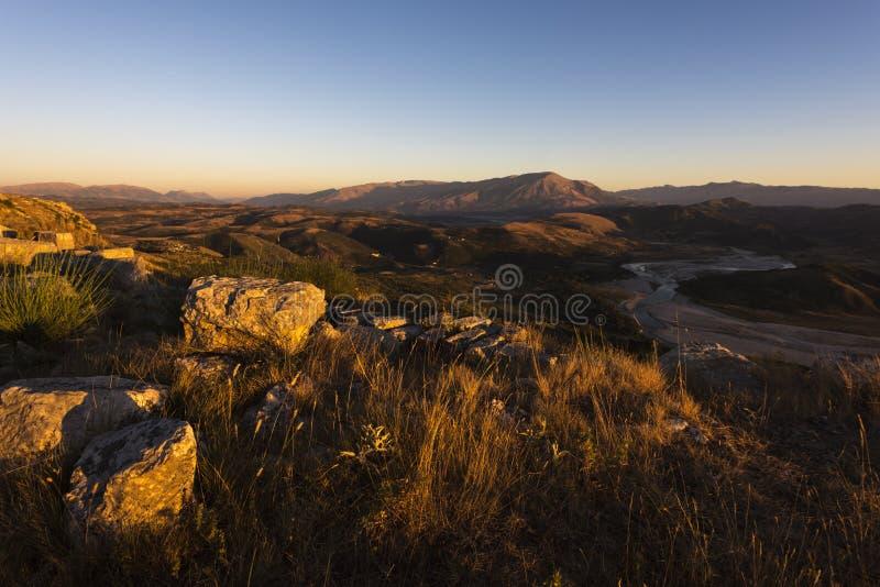 Zonsondergangpanorama uit Byllis-dorp wordt genomen - mening van landschap met stenen, rivierband en bergen, Byllis, Albanië dat royalty-vrije stock foto's