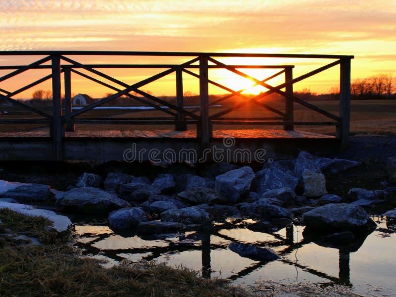 Zonsondergangscène met nog het Lopen van Brug over water, met Bezinning stock afbeeldingen