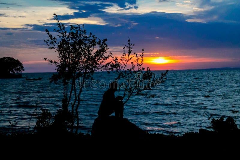 Zonsondergangsilhouet van een zittingsmeisje bij de meerkust royalty-vrije stock fotografie