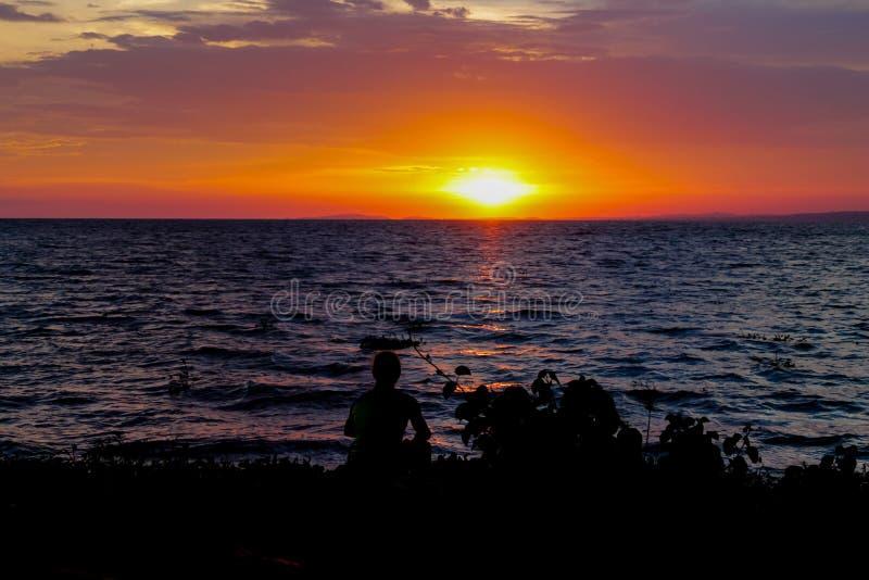 Zonsondergangsilhouet van een zittingsmens bij de meerkust royalty-vrije stock foto