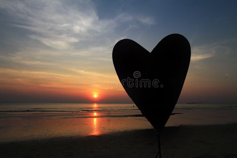 Zonsondergangsilhouet van hartvorm stock foto's