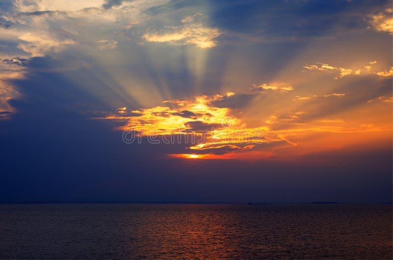 Zonsondergangstralen door een bewolkte donkere hemel over het meer royalty-vrije stock fotografie